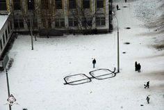 Door het tekenen van een bril in de sneeuw wordt een lantaarnpaal een brillenpoot