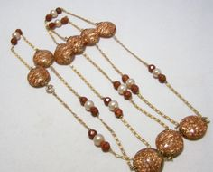 Vintage Art Deco Venetian aventurine art glass disk bead necklace •8 one inch round tablet beads, with copper aventurine swirled center, cased in clear glass •Smaller glass beads and faux pearl beads, 2 inch gold tone chain between each bead •Thumbless c clasp may be gold filled, but it is unsigned •This is an amazing necklace, Ive never seen one like it •Wear single, doubled, or tripled •Good vintage condition, no cracks or other damage to the beads •I special in vintage beaded jewelry…