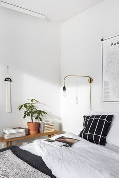 love the singular accent pillow and plant in a terra cotta pot. Love the wooden nightstand and the way it's styled. Also love the black and white motif in the bedding.