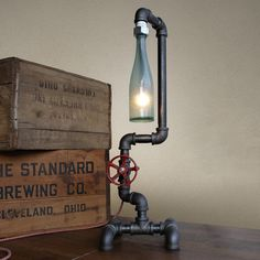 This lamp is constructed from industrial style black iron piping. The vintage bottle is firmly secured by custom rubber gaskets that grasp the bottle without causing damage.  A low wattage bulb is used to illuminate the vintage amber bottle producing a warm ambient light.  A rotating faucet handle serves as a switch to turn the light on and off. Power is supplied by a retro-style cloth covered lamp cord and plug.-Number of bulbs: 2-15 Watt-Cord length: 8'-Socket: Candelabra Please allow…