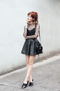Um look preto, mas cheio de texturas e detalhes. Com saia de couro, blusa com transparência, sobreposição e sapatinho de verniz.