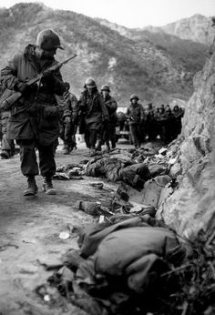Marines marching past bodies, the Korean War happened when North Korea invaded south Korea with the influence and armament of the USSR with tanks and machine guns and aircraft to have a spread ed influence of communism into democratic countries but like the Vietnam war indirect confrontation by the US and USSR