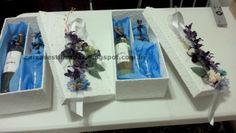 Caixa padrinho, com vinhos, uma taça e dois bem casados.