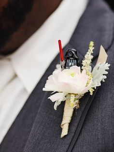 Don Darth Vader as a Lego figurine on the groom's boutonniere to playfully showcase his Star Wars fandom.