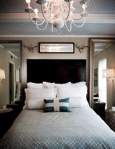 Dwa duże lustra po dwóch stronach łóżka w sypialni.
