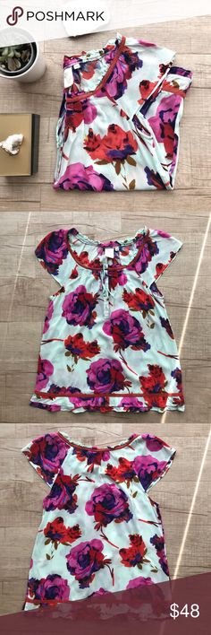 """Eloise(Anthropologie)Ruffled Hem Cap Sleeve Blouse • Eloise for Anthropologie Floral Printed Cap Sleeve Sleep Top • Front half button closure, w/ ties • Delicate ruffled hem w/ crochet trim • Light blue with fuchsia flowers  • BUST (laid flat, on one side) - 16"""" • LENGTH - 25"""" • 100% Rayon  • Please note, there is one small spot of discoloration, as pictured.  • Otherwise in excellent used condition            🌵all measurements are approximate  🌵no trades/paypal/off site transactions…"""