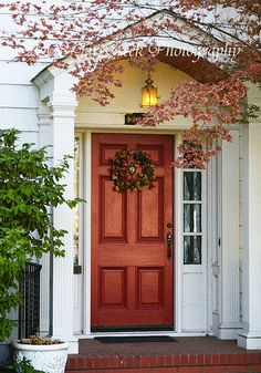 Pretty entrance: Portico, red door, wreath. {{I want to add a portico or porch with roof to the front of my house. I'm thinking of painting my door this color. The house was bought with pale yellow siding and has black shutters on the front windows (two story). I think I need to take a pic of my house then photoshop different paint samples to make up my mind! Need to paint the shutters too!}}