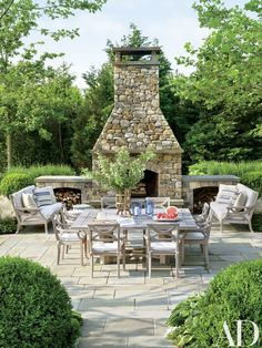 Arranged near the outdoor fireplace are Country Casual sofas and chairs cushioned in a Sunbrella fabric | archdigest.com