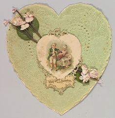 "Heart-shaped valentines card, 1850–99. The Metropolitan Museum of Art, New York. Gift of Morrison H. Heckscher, 1989 (1989.1154 (2)) | This Valentines card, shaped like a heart and clad in green lace, depicts a heart-shaped image of a boy and girl in the center, combined with the text ""with love and devotion"". The card is further decorated with fake (partly textile) twigs of cherry blossom."