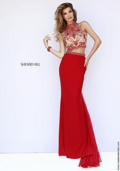 New for 2015...Nude lace runs the crop top decking the two-piece ensemble of Sherri Hill 11212 prom dress, enhanced with a lavish spread of intricate floral beadwork. A teardrop cutout graces the zipped-up rear, complementing the bare midriff. Matching beads build into a slim band hugging the natural waist, where the full length fluted skirt is anchored, finished with a gathered panel train. Also available in White, Black and Royal.