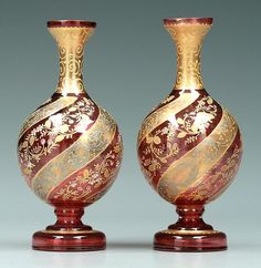 Pair Moser vases: dark cranberry with spiral gilt and enamel floral bands, early to mid 20th century, 7-5/8 in.