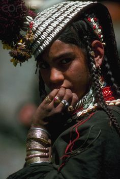A Kalash girl of northern Pakistan wears bracelets and rings, as well as a traditional headdress decorated with shells and beads. Chitral, Pakistan | © Ric Ergenbright/Corbis