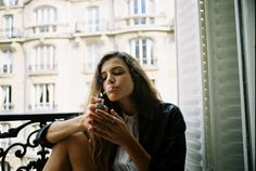 girl smoking in a window.