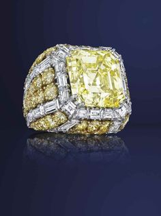An approximately 23.56 carats square step-cut fancy intense yellow diamond and diamond ring, by David Webb