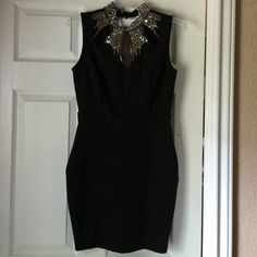 Black Blingy Collared Dress Black dress with silver blingy collar, the back is a V cut out, it is 95% polyester/5% spandex, it does stretch a little to form fit. The perfect dress for any occasion! Bought 2 for a wedding reception ( not sure of size) this one is brand new, never worn! Symphony Dresses Backless
