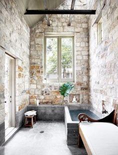 Salle de bain avec une baignoire en marbre bleu, sa charpente apparente, son mobilier vintage et ses murs de pierre blanche