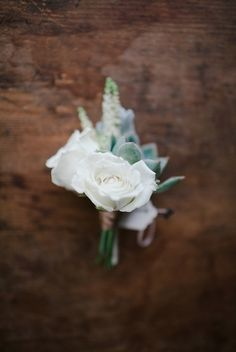 The groom's boutonniere will be a white ranunculus, succulent, and seasonal greenery wrapped in raffia with the stems showing.