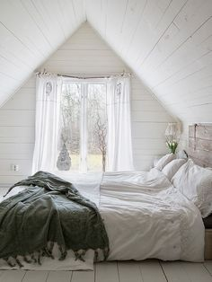 Attic bedroom with white plank walls