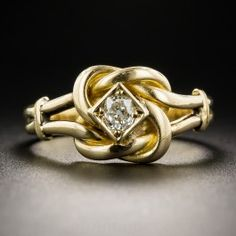 A bright and shining antique cushion-cut diamond ties the knot of this lovely ring, hand fabricated in 18K yellow gold, dating back to the early days of the last century. More than likely of British origin, it measures 7/16 inch and is currently ring size 7 1/2.