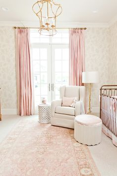 Pink curtains, gold chandelier, white rocking chair and French-inspired walls of nursery