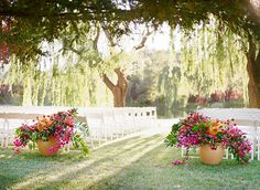 Bold Mediterranean Inspired Wedding at Black Swan Lake. Lush bougainvillea floral centerpieces set among crisp white chairs underneath a canopy of whispering willow trees. Wedding ceremony inspiration. Bold wedding inspiration. Pink wedding inspiration. Bougainvillea and weddings.