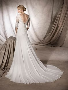 Halima WEDDING DRESSES 2017 Marvellous flare wedding dress in georgette with a sensual V-neckline and elbow length sleeves, embellished with Chantilly and guipure appliqué that flow over the back and hip.