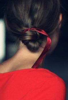 Add a delicate red ribbon to your low bun for feminine flair.