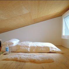 Chambre dans une soupente en contreplaqué avec tapis en mouton dans la maison de new-york
