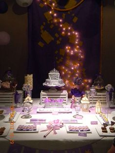 Purple backdrop with yellow paper squares as lanterns and the fairy lights behind it