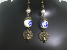 White n blue ceramic beads with bronzen peacock dangles and antique bronze bead caps