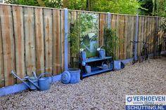 Een schutting die perfect past in een tuin met een landelijke stijl. Door de grote schaaldelen als plank en de grijze betonpalen heeft deze tuinafscheiding een zeer robuust en duurzaam karakter.
