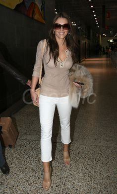 Liz Hurley arrives in Melbourne to meet Shane Warne. Liz does this simple look well. Tight white trousers and simple top.