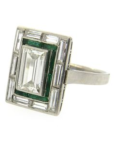 An Exquisite Art Deco Emerald, Diamond and Platinum Engagement Ring, 1920s. Centring an emerald-cut diamond, approximately 2ct VS1-H, surrounded by ten baguette-cut diamonds and emeralds.