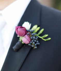 Celebrate the lush beauty of the season with a summer wedding boutonniere with viburnum berries, freesia, and pink ranunculus. This purple boutonniere pairs well with a navy suit.