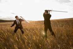 Angry businessmen fighting with sword and shield in field