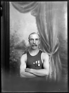 Studio upper torso portrait of unidentified sportsman with large moustache wearing a singlet with three medals, Christchurch