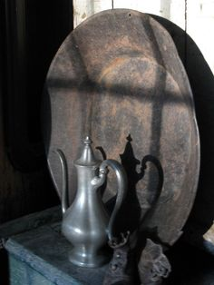 Pewter teapot shadow reflects on the old gold miners pan from the shadow produced by the french doors. HighButtonShoe farmhouse.