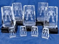 """Custom recognition awards created for NASA for their OPTIMUS PRIME Spinoff Video conquest. This contest encourages students to produce short, creative videos about their favorite technology from NASA's Spinoff Publication. The custom trophies designed by Bennett Awards were based on Bennett's """"Crystal Honor"""" awards, which feature a clear crystal polyhedron embedded with a custom-designed, 3D opaque object. The customized object used by NASA was a 3D image of the transformer """"OPRIMUS PRIME""""."""