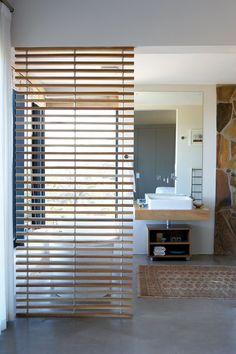 The slatted wooden room divider in the bathroom in the honeymoon suite was made by Leslie Philander and the woodwork supporting the basin by Isgak Hull.