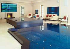 Want a pool? How about one in the middle of your house?   In this 2,200-square-foot room, you'll find this stunning 48-foot-long pool, a 123-inch flat-screen home theater system and an unusual combination fireplace and waterfall, among many other spectacular decorative touches. See more pictures of this project here.
