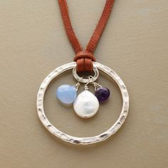 """CELESTIAL CIRCLE NECKLACE--A hammered sterling circle shelters a sky blue chalcedony briolette, stormy faceted amethyst and cloud-like freshwater cultured pearl. Brown leather thong fastens with a sterling silver button and loop. Handcrafted in USA. Exclusive. 1-5/8"""" Dia."""