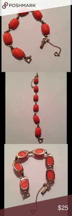 """Vintage Lucite Scarab Bracelet Vintage molded lucite Scarab Bracelet. Gold Tone with coral colored scarabs with Egyptian like marking on the back. Fold over style clasp with a Safety Catch Chain. No markings. Measures 7 1/2"""" long Vintage Jewelry Bracelets"""