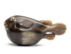 A buffalo-horn netsuke of a fugu fish, 19th century Facing ahead as it swims, its tail trailing at the back and its open mouth with inlaid teeth, the eyes of raden with dark horn pupils, unsigned.