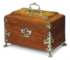 A GEORGE II SILVER-MOUNTED PADOUK TEA CADDY THE MOUNTS WITH UNTRACED MAKER'S MARK IA (SCRIPT), CIRCA 1750 -  The hinged lid with central handle enclosing four stationary compartments, on claw feet 7 in. (18 cm.) high; 10 in. (25 cm.) wide; 6¾ in. (17 cm.) deep