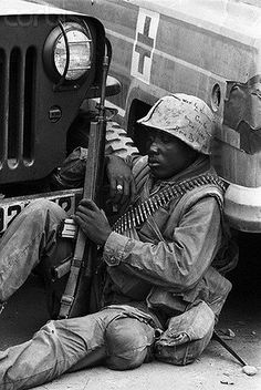 09 Feb 1968, Hue, South Vietnam --- HUE, SOUTH VIETNAM-2/9/68-:  With ammunition slung over his shoulder and a rifle in his hand, this American GI has a quiet moment for thought during a pause in the fighting at Hue. A week after the first enemy assault in this area, allied forces were making slow progress in clearing Hue of Viet Cong and North Vietnamese troops. ---