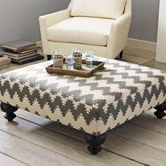Make an ottoman from a pallet, foam, table legs, fabric and a staple gun.