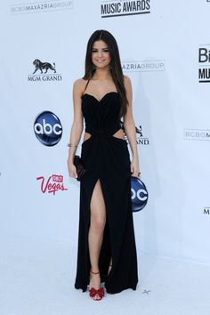 Fashion icon: Selena Gomez. Black gown with cut outs and high slit.