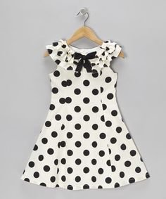 Crafted out of breezy cotton, this dress is covered in playful polka dots and sports a pretty bow embellishment that will have sweethearts swooning.
