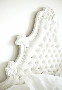 White on white on white #bedroom with #tufted headboard and ornate detailing