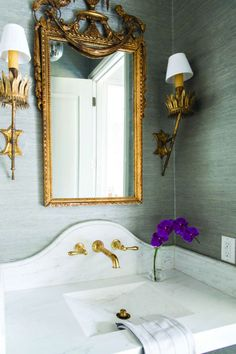 Gorgeous powder room features walls clad in gray grasscloth lined with an Alabama White marble top vanity and sink paired with a curved marble backsplash lined with a gold faucet under a gilt mirror illuminated by French brass wall sconces. Gold Bathroom, Grey Bathrooms, Beautiful Bathrooms, Design Bathroom, Bad Inspiration, Bathroom Inspiration, Home Design, Gold Bad, Home Luxury